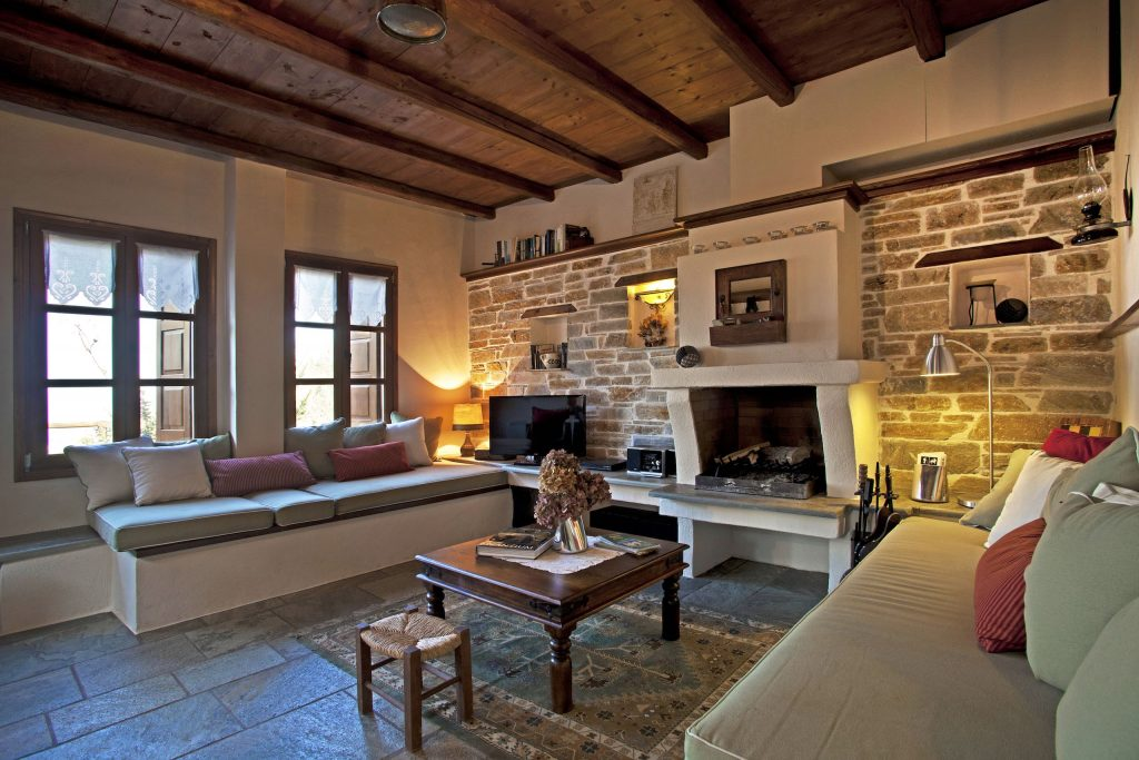 Two sofas by the fireplace in family villa with a garden, the Villa Dioni in Pelion.