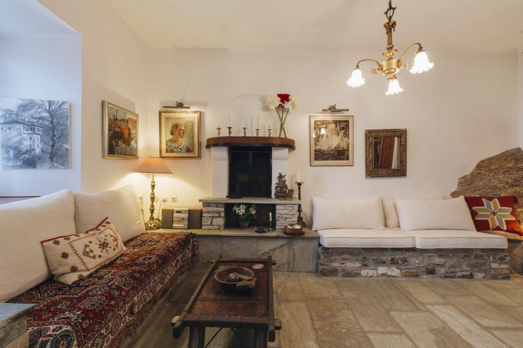 Two built-in sofas, a small table and fireplace in the sitting room of Villa Koukouvara in Pelion.