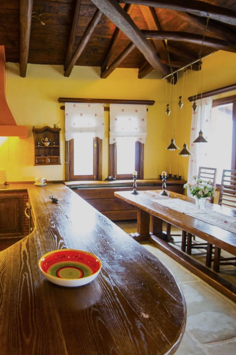 The wooden kitchen counter and the dining room of Villa 2 Cypresses in Pelion with sea views.