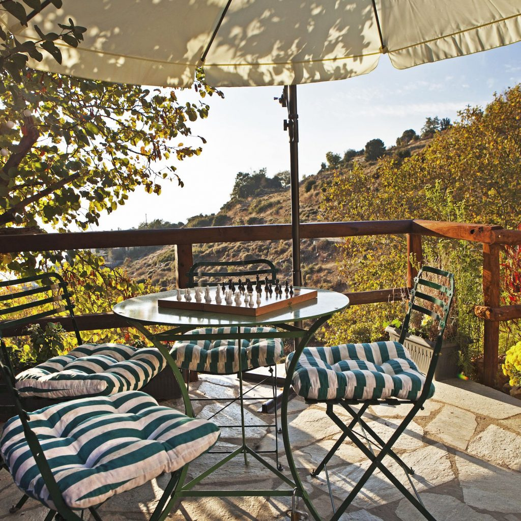 Pillows on chairs and a round table on the terrace of Villa Thalia in Pelion with sea views.