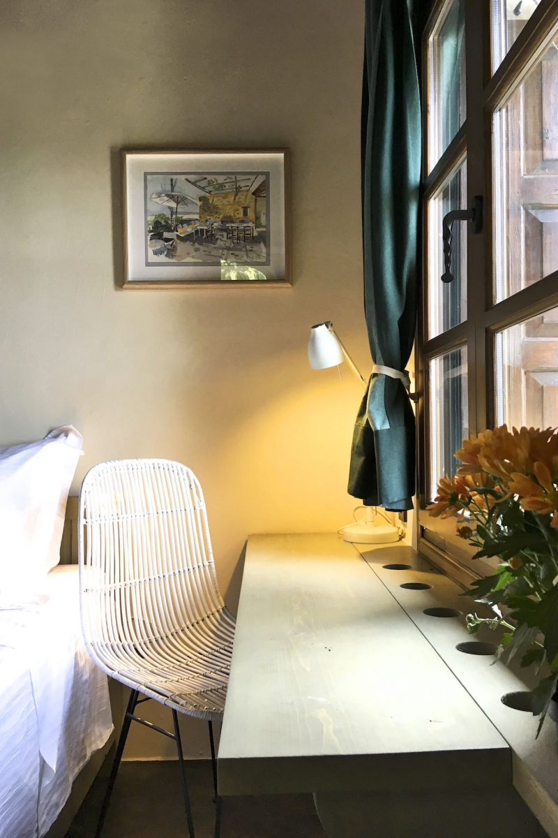 A desk for reading by the window, chair and a picture on the wall in Villa Iris in Pelion.