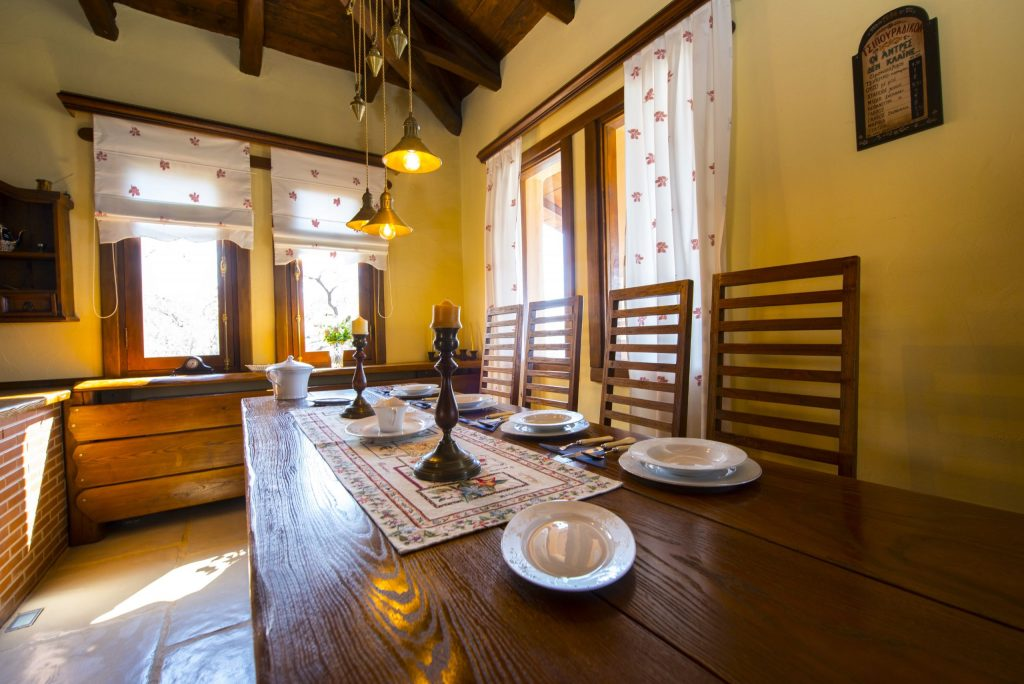 Dishes and candlesticks on the table by the window in luxury Villa 2 Cypresses in Pelion.