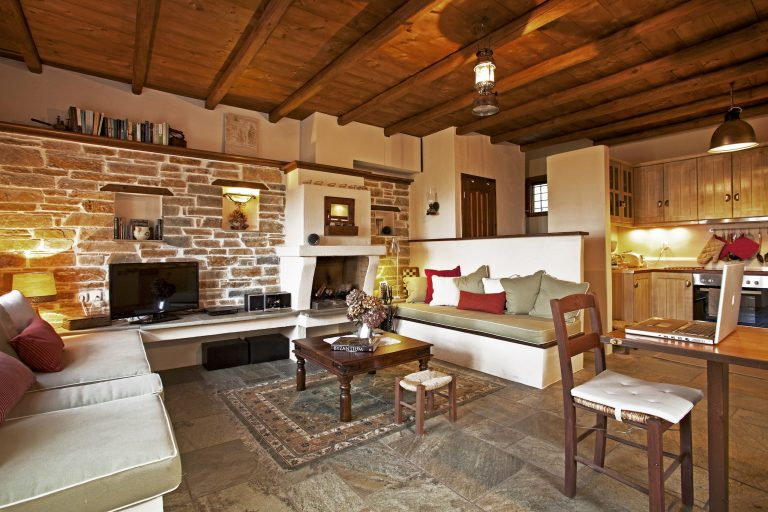 In the living room of Villa Dioni in Pelion there is a fireplace and two built-in sofas.