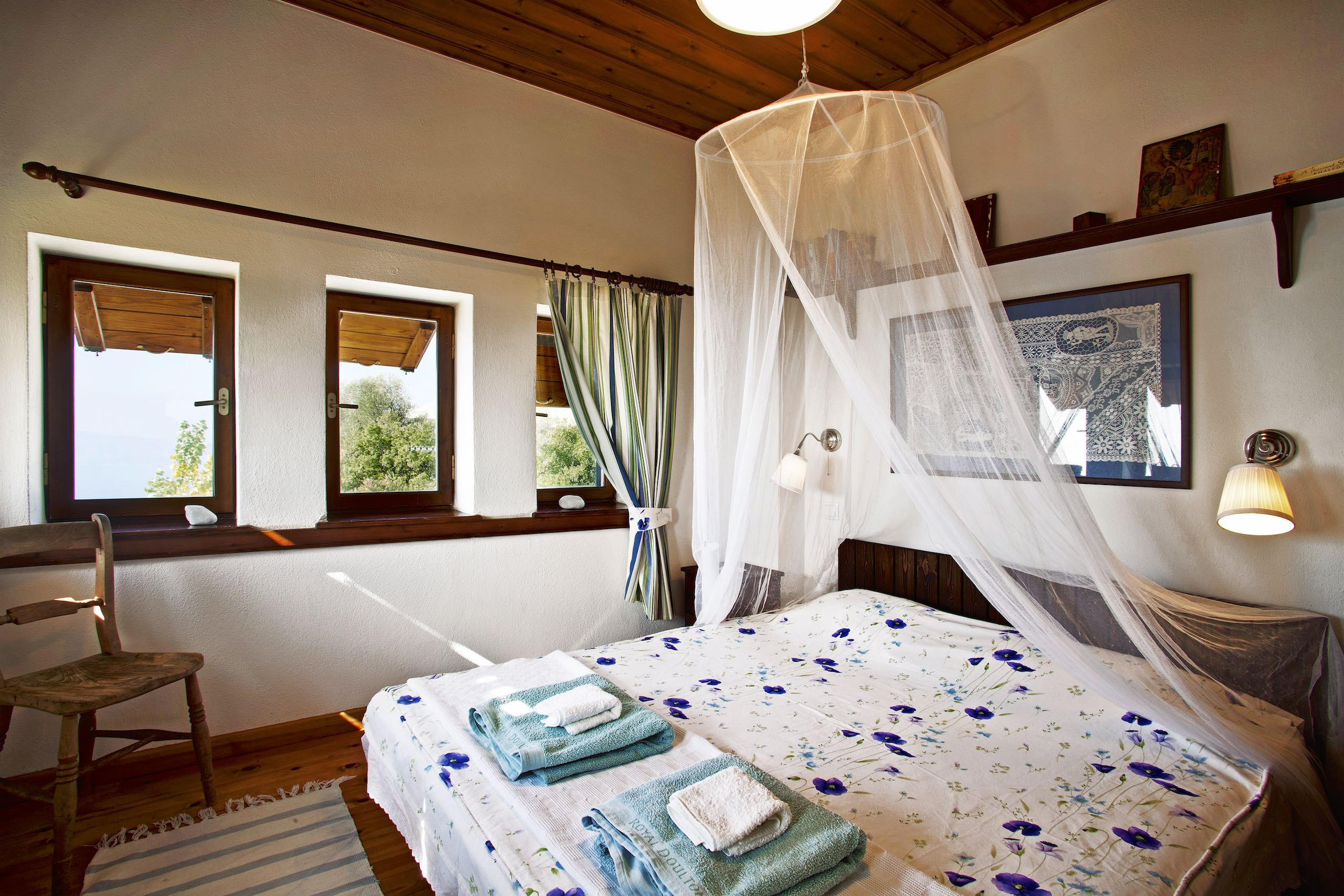 Towels on the double bed with a mosquito net in Villa Selini in Pelion.