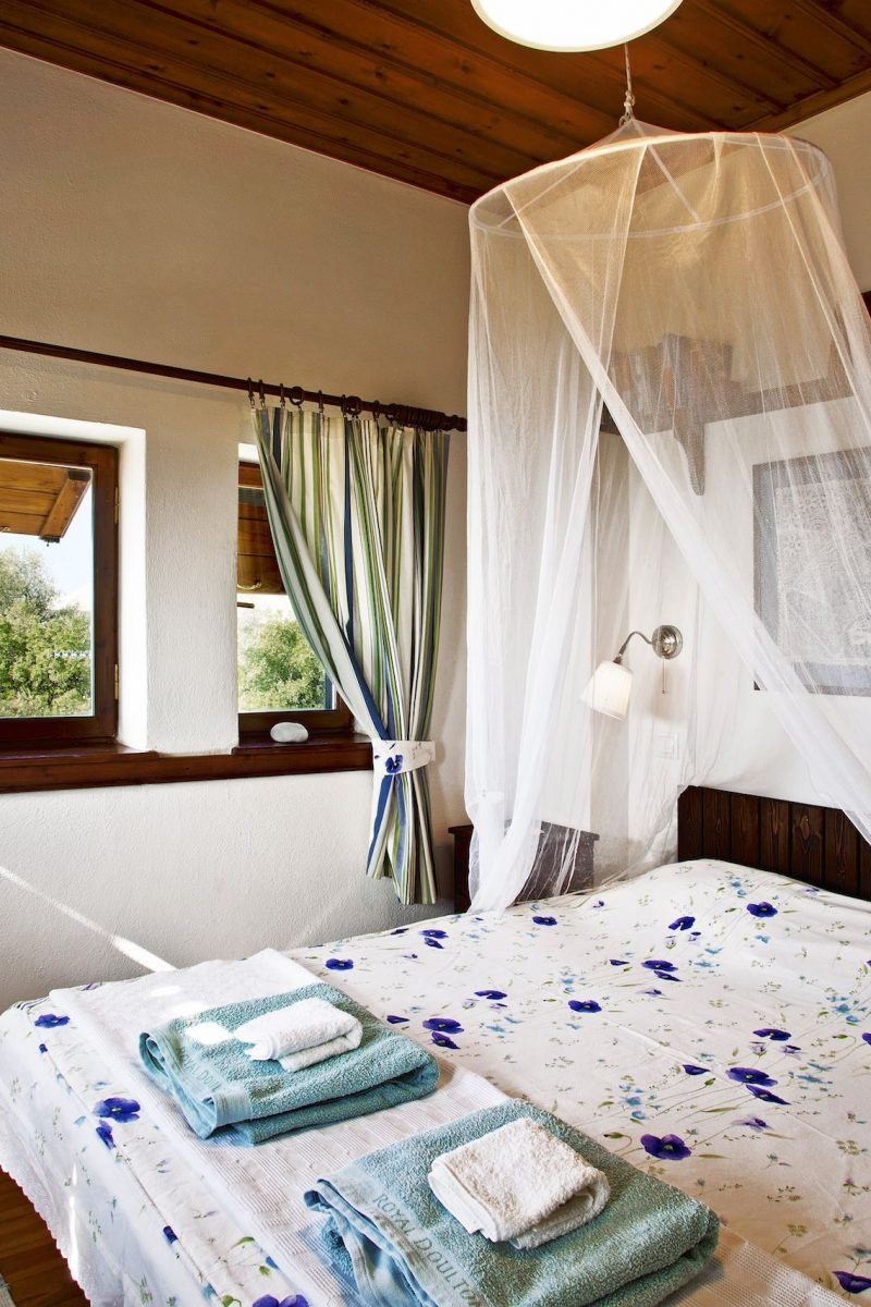 Towels on the bed and a traditional knitting on the wall in Villa Selini in Pelion.